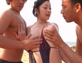 Attractive beach queen Minako Komukai has threesome sex outdoors